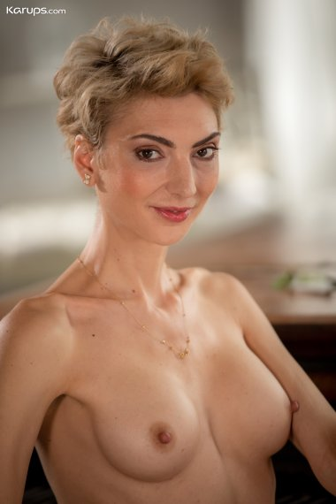 Super fit blonde MILF Natalie Anna sits naked at her piano