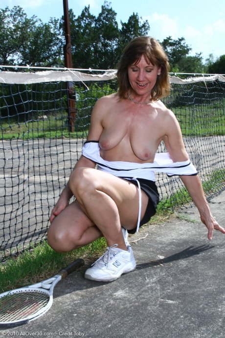 Brunette mature housewife shows off her shaved pussy in outside