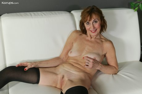 Mature redhead Amy D posing naked in only her black stockings